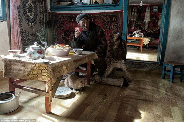 Фото охотника с орлом в своем доме в Монголии.