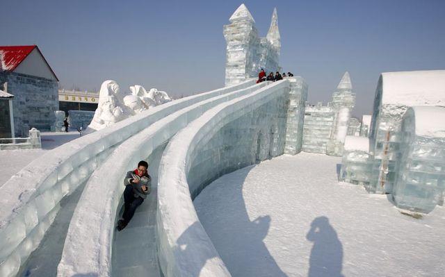 Посетители скатываются по одной из многочисленных ледяных горок фестиваля