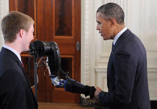 Президент США Барак Обама пожимает руку робота