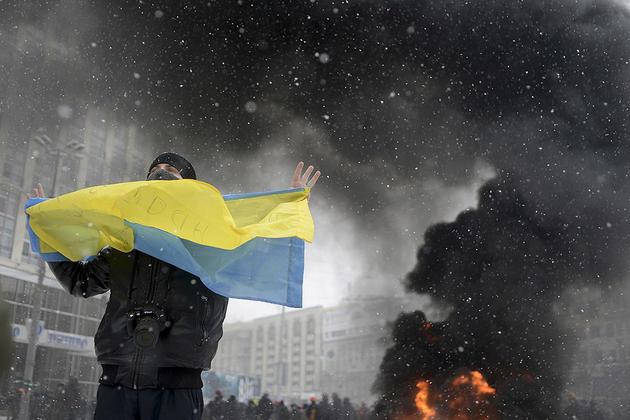 A man holds a Ukrainian flag as smoke rises in the background during clashes between police and pro-European protesters in Kiev