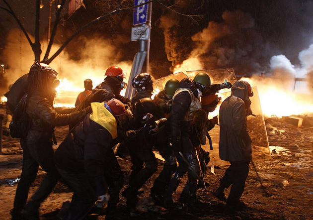 Pro-European protesters take cover behind shields during clashes with riot police in Kiev