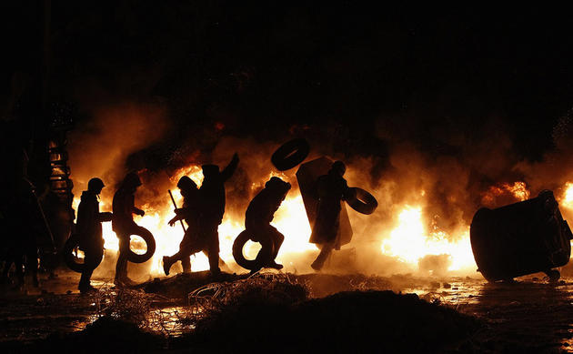 Pro-European protesters throw tyres into a fire during street violence in Kiev